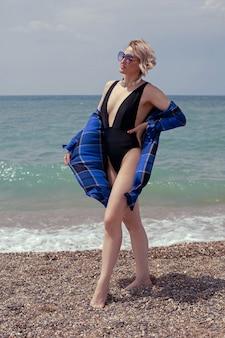 Seksowna kobieta w srebrnym kostiumie kąpielowym i okularach przeciwsłonecznych stoi na plaży