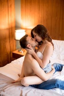 Seksowna kobieta w staniku siedzą na przystojnym facecie i obejmują go nogami na łóżku