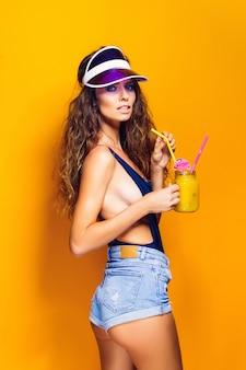 Seksowna kobieta w strojach kąpielowych i niebieskich dżinsach, modny daszek trzyma szklankę świeżego napoju, stojąc na gorącej żółtej, pomarańczowej scenie