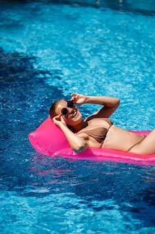 Seksowna kobieta w stroju kąpielowym leży na różowym dmuchanym materacu w basenie. zrelaksuj się przy basenie w upalny, słoneczny dzień. koncepcja wakacji