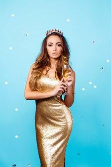 Seksowna kobieta w złotej sukni i koronie z szampanem
