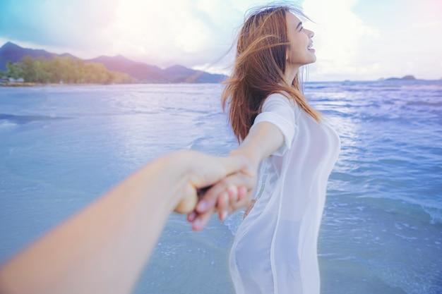 Seksowna kobieta wolność wakacje relaks na plaży para trzymająca się razem za ręce