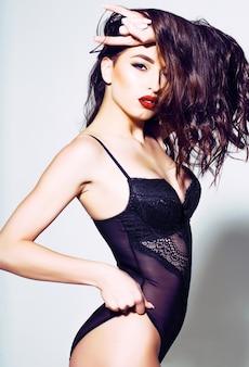 Seksowna kobieta z czerwonymi ustami w czarnym staniku ma tatuaż