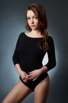 Seksowna kobieta z długimi nogami i włosy pozuje na zmroku. piękne oczy i czysta gładka skóra
