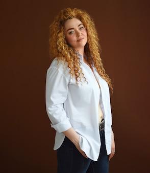 Seksowna kobieta z długimi rudymi włosami młoda dziewczyna w rozpiętej białej koszuli