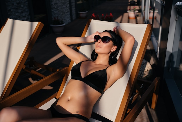 Seksowna kobieta z dopasowanym ciałem w modny elegancki strój kąpielowy bikini i okulary przeciwsłoneczne.