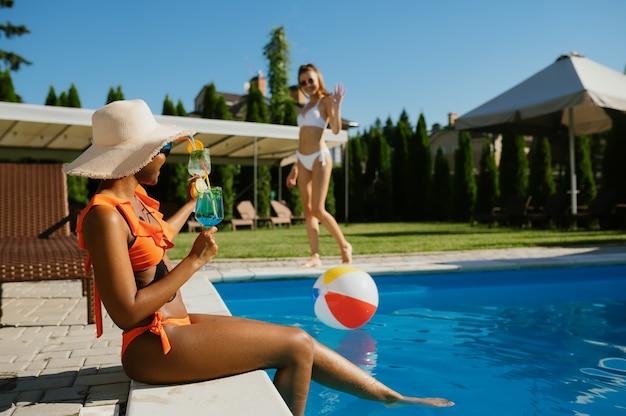 Seksowna kobieta z koktajlem, siedząc na skraju basenu. szczęśliwi ludzie bawią się na letnie wakacje, impreza świąteczna przy basenie na świeżym powietrzu. kobieta spędza czas wolny w ośrodku