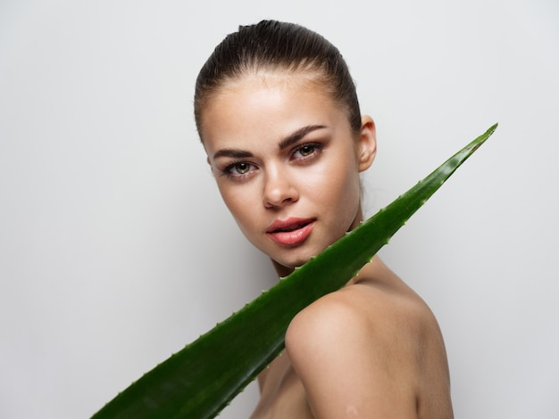 Seksowna kobieta z liśćmi aloesu moda fryzura jasne tło czysta skóra kosmetyki na twarzy