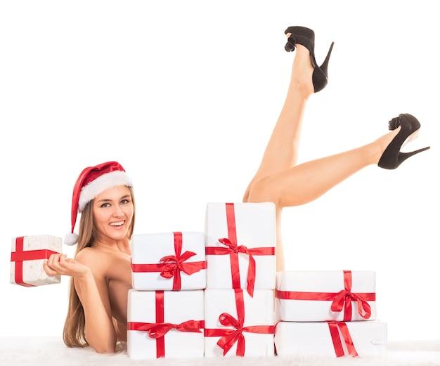 Seksowna kobieta z prezentami świątecznymi leżąca na dywanie, uśmiechnięta i patrząca w kamerę