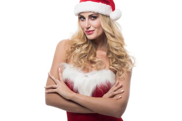 Seksowna kobieta z santa hat pozowanie na białej ścianie