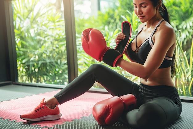 Seksowna kobieta zawiązuje taśmę wokół dłoni, zanim dostanie rękawice bokserskie przygotowujące się do treningu bokserskiego