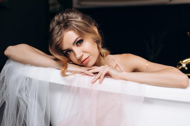Seksowna młoda blondynka w musującej bieliźnie leży w łazience pokrytej jedwabiem