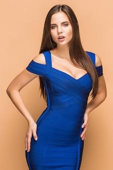 Seksowna młoda brunetka kobieta pozuje w niebieskiej sukience w studio na brązowym tle