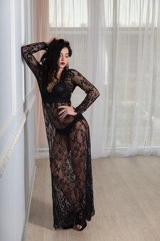 Seksowna młoda brunetka kobieta w czarnej koronkowej sukni. piękna dziewczyna z atrakcyjnym ciałem.