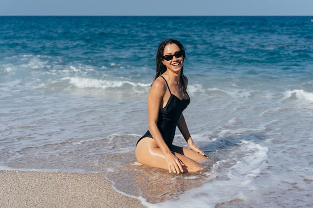 Seksowna młoda brunetka pozuje na jej kolanach w morzu