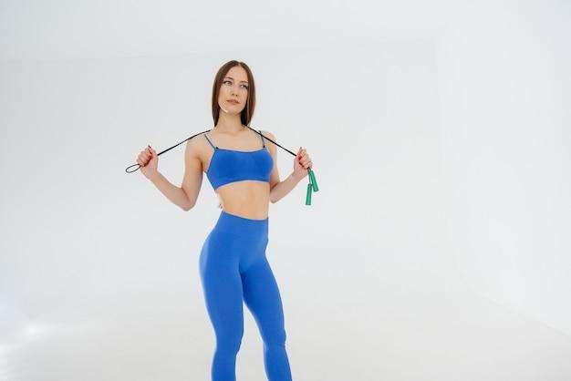 Seksowna młoda dziewczyna skacze przez skakankę w niebieskim dresie na białym tle. fitness, zdrowy tryb życia.