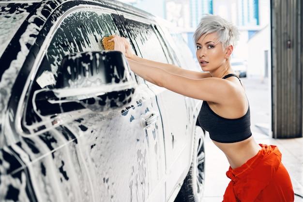 Seksowna młoda kobieta myje samochód w myjni samochodowej