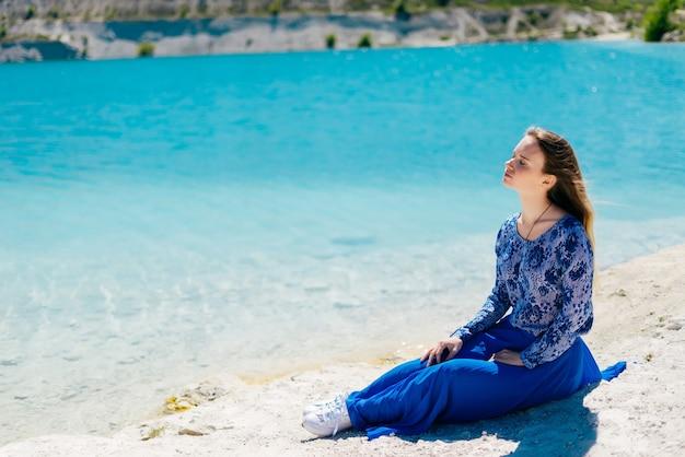 Seksowna młoda kobieta podróżnik siedzi na plaży, relaks, patrząc na tło niebieskiej wody copyspace. ciesz się letnim blaskiem słońca, wolnością szczęśliwą koncepcją