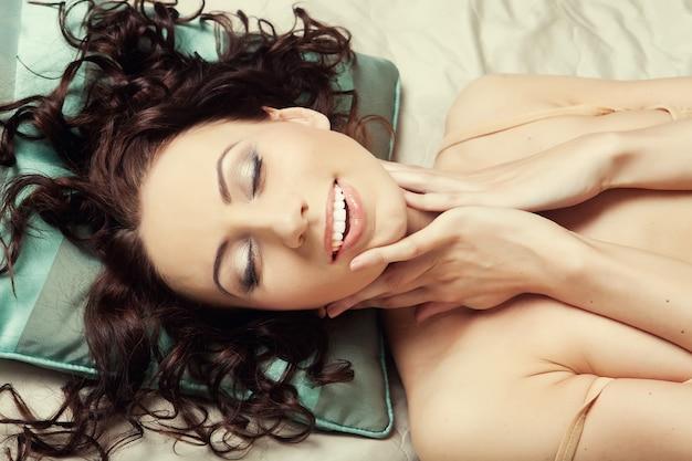 Seksowna młoda kobieta pozuje na łóżku