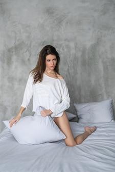 Seksowna młoda kobieta pozuje w łóżku