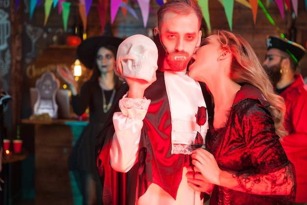 Seksowna młoda kobieta przebrana za wampira gryzącego szyję mężczyzny przebrana za drakulę na halloween. dracula trzyma ludzką czaszkę.