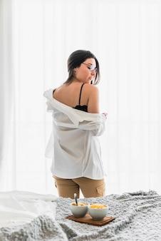 Seksowna młoda kobieta stoi za łóżkiem ze śniadaniem na łóżku