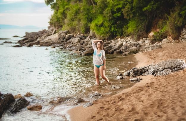 Seksowna młoda kobieta stojąca na pięknej plaży w czarnogórze