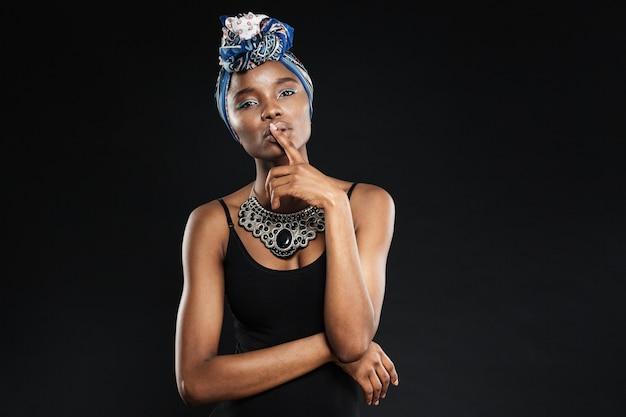Seksowna młoda kobieta trzymająca palec przy ustach w geście milczenia