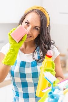 Seksowna młoda kobieta uśmiechając się do kamery, trzymając gąbkę do mycia naczyń w gumowych rękawiczkach, częściowo zakrywając twarz. trzymając detergent w drugiej ręce, mając przed sobą więcej środków czyszczących.