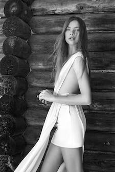Seksowna młoda kobieta w lekkiej białej sukni pozuje w wiosce blisko starego domu. kobieta o idealnej figurze na ścianie wiejskiego domu z bali