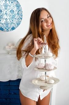 Seksowna młoda kobieta w męskiej koszuli trzyma tacę słodyczy przy kominku