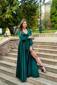 Seksowna młoda kobieta w modnej długiej zielonej sukni cieszyć się słonecznym letnim dniem, na świeżym powietrzu