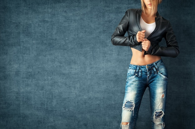 Seksowna młoda kobieta w modnych ubraniach na ścianie grunge