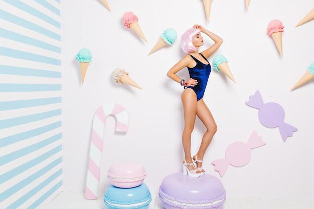 Seksowna młoda kobieta w niebieskim body, na obcasach, z różową ściętą fryzurą, stojąca na wielkim macaron wśród słodyczy. radosna modelka, relaks, słodki styl życia, zamknięte oczy.