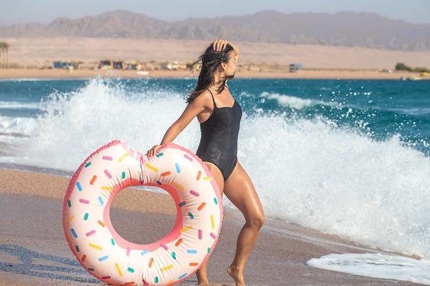 Seksowna młoda kobieta z kółeczkiem w kształcie pączka nad morzem. pojęcie wypoczynku i rozrywki na wakacjach.