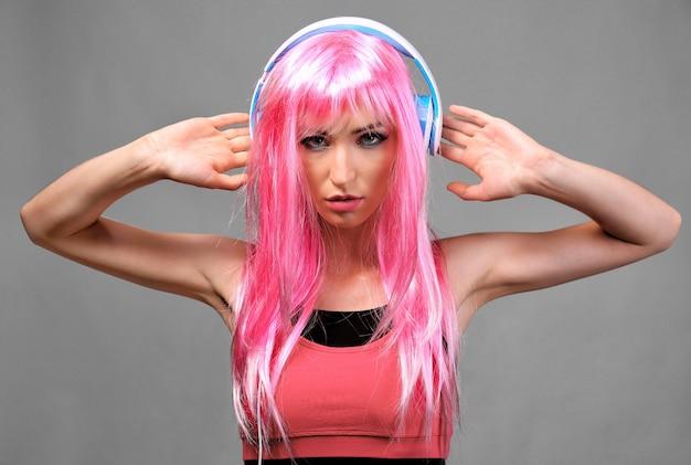 Seksowna młoda kobieta ze słuchawkami na szaro