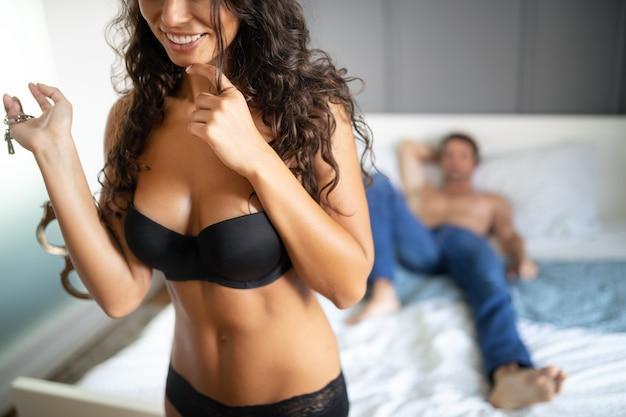 Seksowna młoda para namiętna i bawiąca się w sypialni