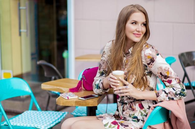 Seksowna młoda stylowa kobieta siedzi w kawiarni