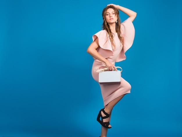 Seksowna młoda stylowa seksowna kobieta w różowej luksusowej sukience, letni trend w modzie, elegancki styl, niebieskie tło studio, trzymając modną torebkę