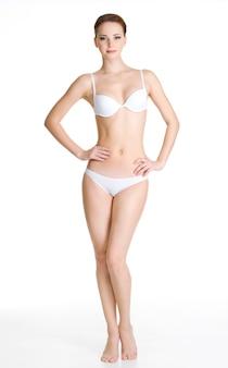 Seksowna młoda szczupła kobieta z pięknym idealnym ciałem, pozowanie na białej przestrzeni. portret pełnometrażowy