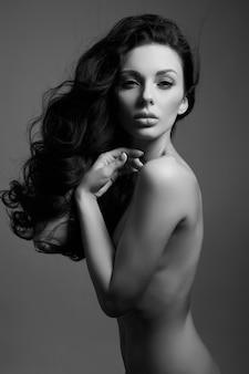 Seksowna moda naga kobieta z długimi włosami, silnymi kręconymi włosami brunetki