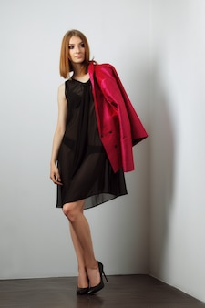 Seksowna modelka w czarnej bieliźnie i przezroczystym szlafroku. gołe nogi i wysokie obcasy.