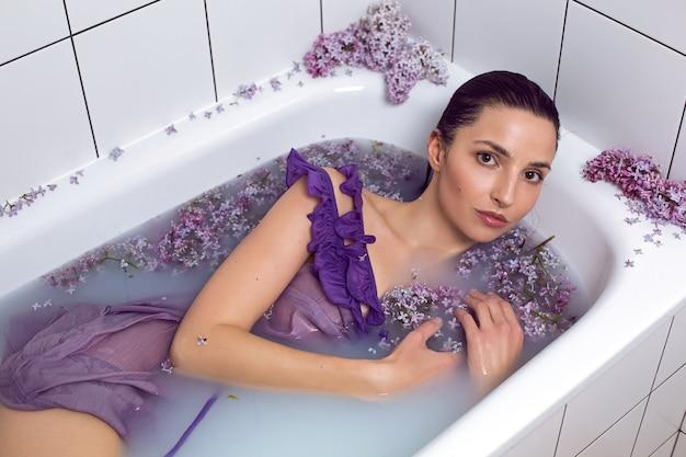Seksowna modna kobieta w stroju kąpielowym leży w białej wannie z mlekiem i kwiatami bzu