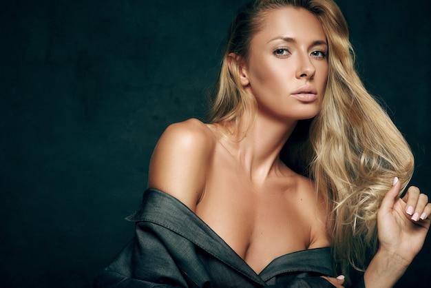 Seksowna modna kobieta z długimi blond włosami w garniturze na nagim ciele na ciemnym tle. kobieta patrzy w kamerę
