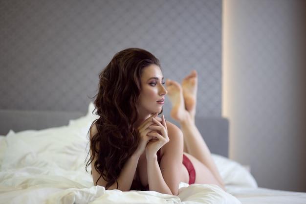 Seksowna niebieskooka brunetka w czerwonej bieliźnie leży na dużym łóżku