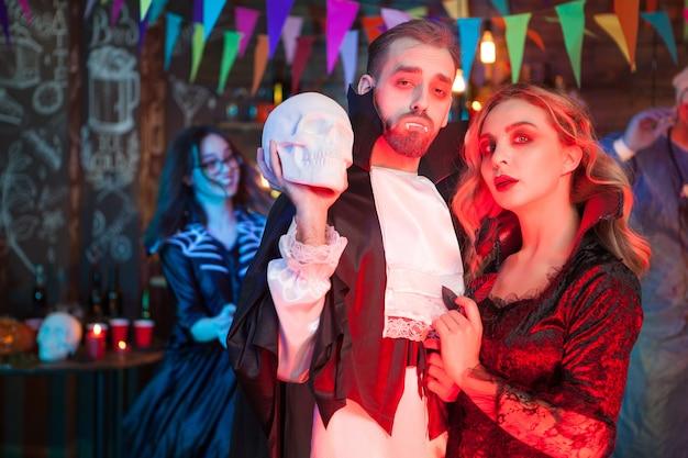 Seksowna para przebrana za wampiry na imprezę z okazji halloween. piękna kobieta przebrana za wampira. seksowny mężczyzna przebrany za draculę.