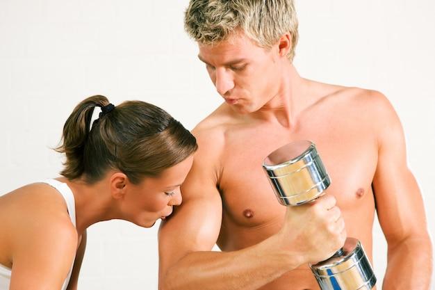 Seksowna para z dumbbells w gym