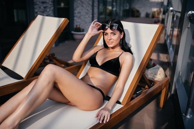 Seksowna piękna brunetka kobieta leżąc na niebieskim tle w zmysłowej czarnej bieliźnie. atrakcyjna modelka z czerwonymi ustami. studio strzał, poziomo