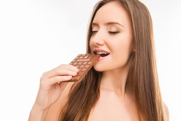 Seksowna piękna dziewczyna namiętnie gryzie mleczną czekoladę
