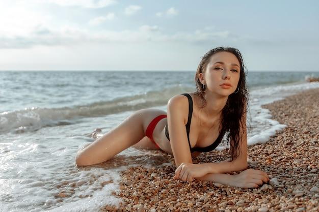 Seksowna piękna dziewczyna w stroju kąpielowym leży na plaży